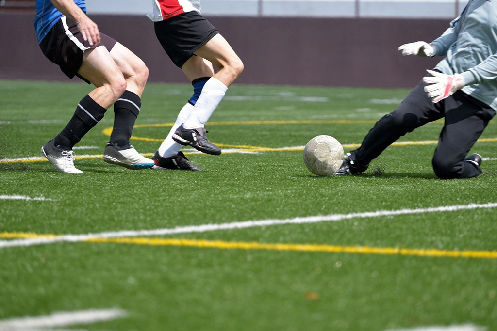 Adult, male, soccer striker, sweeper and goalkeeper going for the ball ** Note: Soft Focus at 100%, best at smaller sizes
